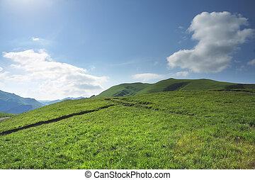 Green hill in Caucasus in sunlight under blue cloudy sky