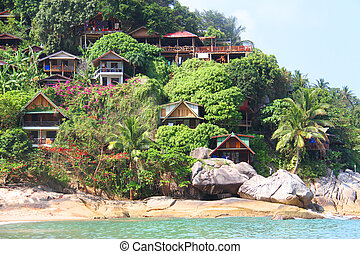 green hill with bungalows on tropical beach