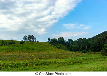 Green hills and blue sky with clouds