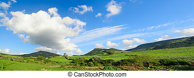 green hills under a blue sky with clouds
