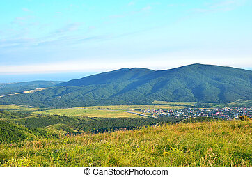Green hills under blue sky in village district of Krasnodar krai, Russia in summer