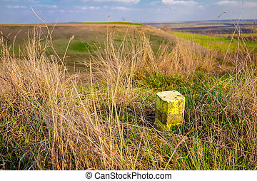 Green hilly landscape and a little concrete pillar on the grass