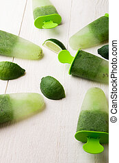 Green homemade ice cream on white wooden background. Fruit ice with kiwi and lime. Top view.