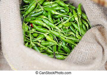 Green hot fresh chili pepper in burlap sack