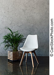Green houseplant in pot and empty white chair indoors