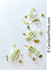 Green ice cream on a stick with a piece of fresh kiwi, mint leaves and ice, presented in the form of a corner frame on a gray marble background with a copy of the space.