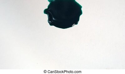Green ink is dripping on white, dry paper. In caprel...