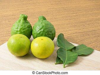 Green Kaffir Lime with Lemon Lime on Cutting Board