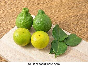 Green Kaffir Lime with Lemon Lime on Wooden Board