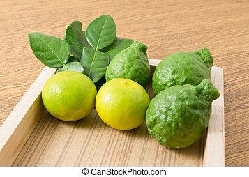 Green Kaffir Lime with Lemon Lime on Wooden Tray