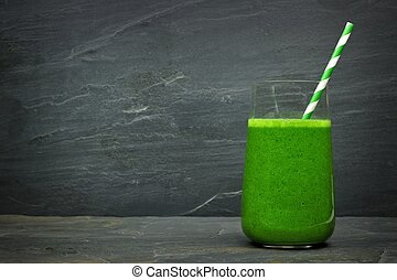 Green kale smoothie in a glass with straw on a dark slate stone background