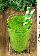 Green kale smoothie in a glass with straws on a rustic wood background