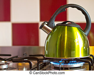 green kettle on a modern stove in front of a red with white...