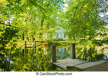 Green landscape in park with old house and bridge under water in pond