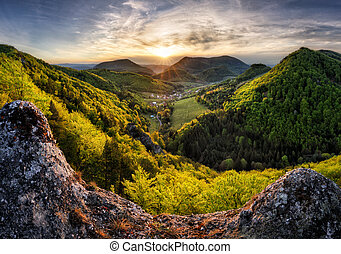 Green landscape with village, mountain and rocks at sunset, Nature