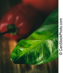 green leaf with red pepper in background on wood