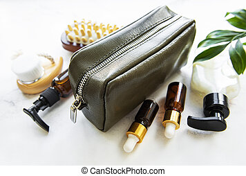 Green leather cosmetic bag and natural cosmetics on white ...