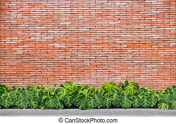 Green leaves with red brick wall background