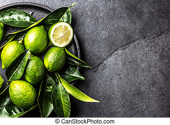 Green lemon Lime with fresh leaves on black plate, slate...