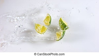Green Lemons, citrus aurantifolia , Fruits falling on Water...