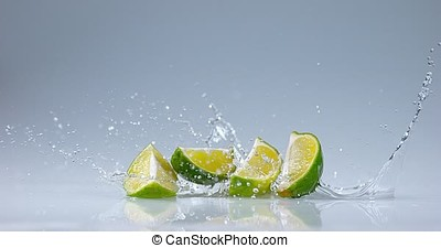Green Lemons, citrus aurantifolia , Fruits falling on Water,...