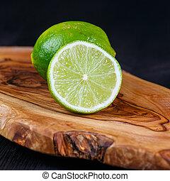 green lemons on the wooden table