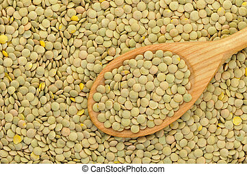 Top view of green lentils in a wooden spoon