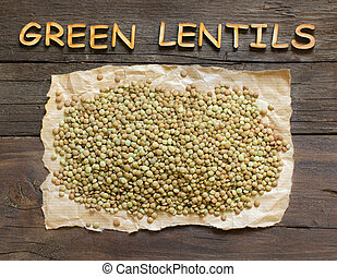 Green lentils on wooden table with wooden word
