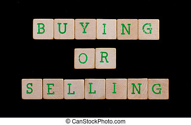 Green letters on old wooden blocks (buying or selling)