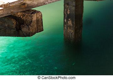 green light on the sea under the wooden bridge pier