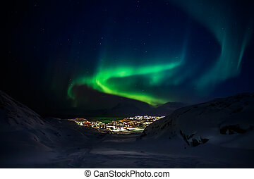 Green lights of Aurora Borealis with shining stars over the mountains and highlighted city, Nuuk, Greenland