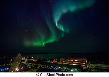 Green lights of Aurora Borealis with shining stars over the night bay and highlighted buildings of Nuuk city, Greenland