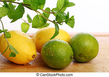 Green lime, yellow lemon and fresh mint on wooden surface
