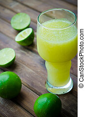 green limes with lime juice in the glass