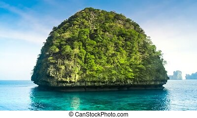 green limestone mountain cliff covered with jungle in ocean...
