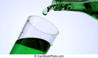 Green liquid pouring into glass