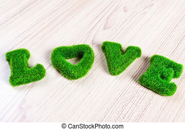 green love wording on wooden floor, made from artificial grass