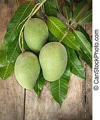 Green mango on wood background