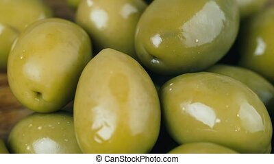 Green marinated olives - Green olives are rotated in front...