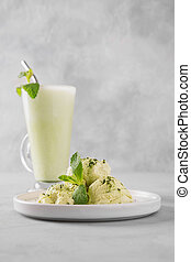 Green matcha ice cream and tea in latte glass on grey table.