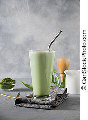 Green matcha tea and milk in latte glass on grey table. Top view. Space for text.