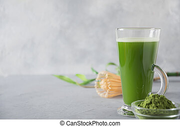 Green matcha tea in latte glass on grey table. Top view. Space for text.