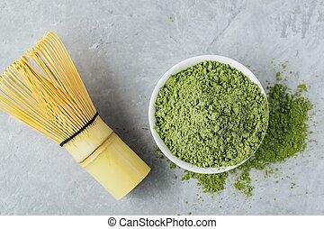 Green matcha tea powder in white bowl