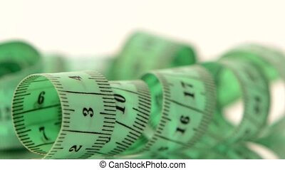 Green measure tape, on white, rotation, reflection, close up