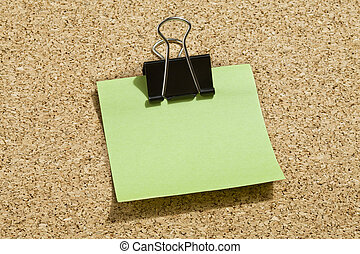 green memo note with binder clip