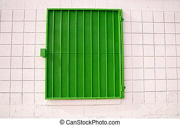 Green mesh shutter on white wall