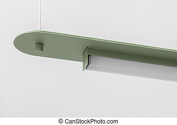 Green metal lamp hanging on gray wall background in studio