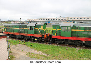 Green metallic iron wheeled freight train, locomotive for the carriage of goods on rails at the railway station
