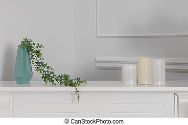 Green modern vase with three candles on white counter