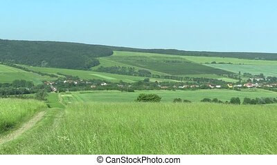Green mountains (meadows), blue sky and village UNESCO Bile Karpaty